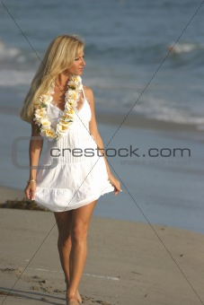 Beautiful Blond walking on the beach in a White dress and a Lei.