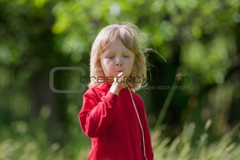 boy with long blond hair and grass straw in the garden