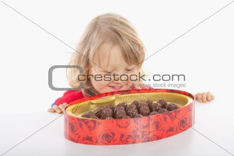 boy with long blond hair and a box of chocolate - isolated on white