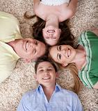 Happy family lying  with their heads close together smiling 
