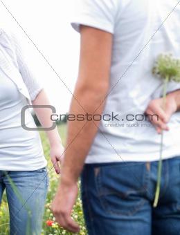 Close up shot of a boyfriend hiding a flower