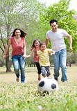 Parents and two young children playing soccer in the green field