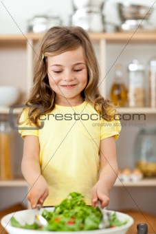 Adorable little child preparing salad in the kitchen