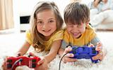 Jolly children playing video games lying on the floor with their parents in the background