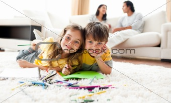 Adorable btother and sister drawing lying on the floor