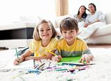 Cute children drawing lying on the floor with their parents in the background