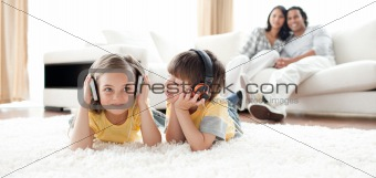 Little boy and little girl playing on the floor with headphones