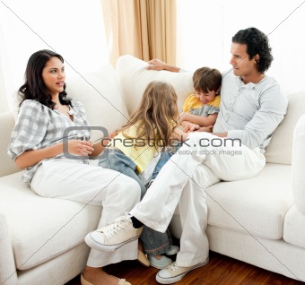 Attentive parents sitting on sofa with their children