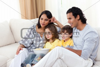 Happy family watching TV on sofa