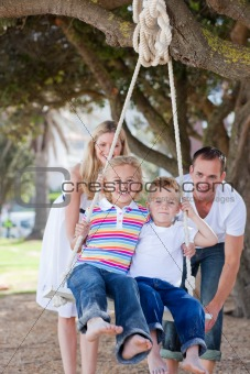 Happy parents pushing their children on a swing