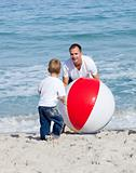 Jolly father and his son playing with a ball