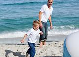 Happy father and his son playing with a ball at the beach