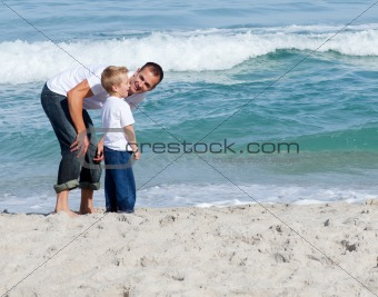 Young father and son playing on a beach