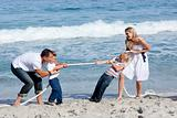 Cheerful family playing tug of war