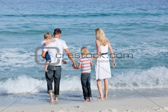 Happy family walking on the sand