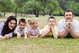 Cheerful family of five lying on lawn in the green park