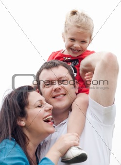 Happy couple with their beautiful daughter sitting on her father's shoulder