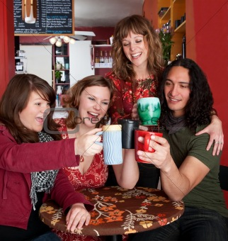 Four young friends toasting at a cafe