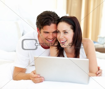 Affectionate couple using laptop