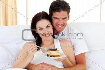 Jolly couple having breakfast