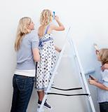 Happy family painting a room with brushes in new house