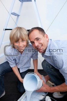 Portrait of smiling father and his son preparing paint