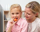 Lively little girl eating fruit with her mother
