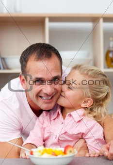 Attentive father eating fruit with his daughter