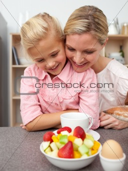 Adorable little girl eating fruit with her mother
