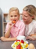 Attractive mother eating fruit with her daughter