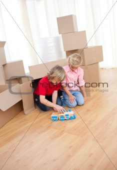 Adorable sibling playing with a train