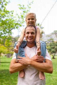 Happy father giving his daughter piggy-back ride