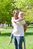 Joyful father giving his daughter piggy-back ride