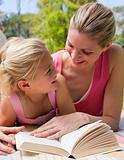 Portrait of a smiling mother and her daughter reading at a picni