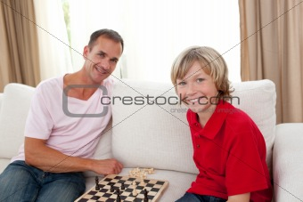 Caring father playing chess with his son