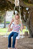 Happy mother pushing her daughter on a swing