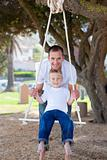 Happy father pushing his son on a swing