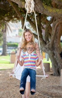 Caring mother pushing her daughter on a swing