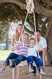 Joyful parents pushing their children on a swing
