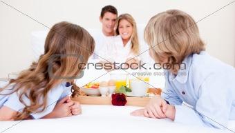 Caucasian family having breakfast sitting on bed