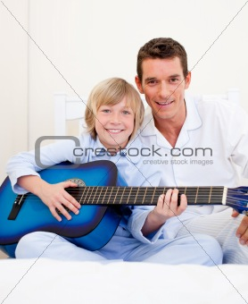 Merry little boy playing guitar with his father in the bedroom