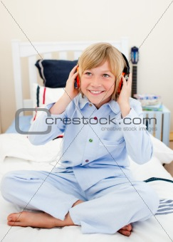 Smiling boy listening music sitting on bed