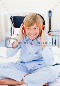 Positive boy listening music sitting on bed