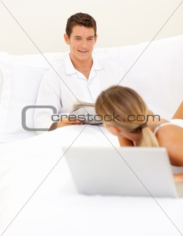 Affectionate couple relaxing on their bed