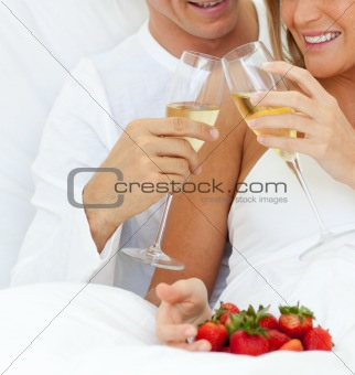 Close-up of a couple drinking Champagne with strawberries