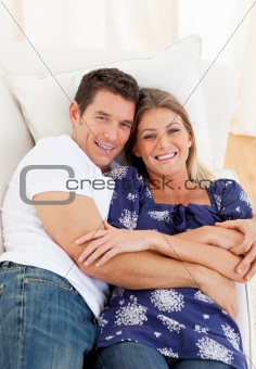 Affectionate couple lying down on sofa