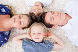 Relaxed family lying in circle on the wall-to-wall carpet