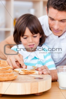 Affectionate father and his son spreading jam on bread