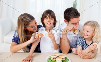 Loving family eating burgers in the living room