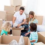 Happy family moving house playing with boxes